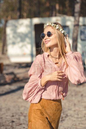 beautiful smiling hippie girl in wreath and sunglasses posing near campervan