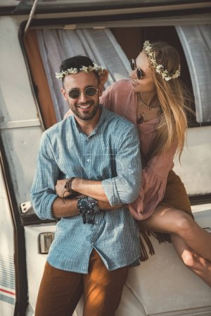 beautiful hippie couple in wreaths and sunglasses embracing and sitting on campervan