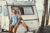 hippie couple in wreaths and sunglasses hugging and sitting on trailer near sea