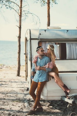 hippie couple in wreaths and sunglasses embracing and sitting on trailer