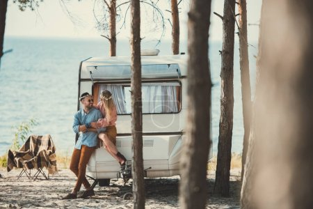 hippie couple in wreaths embracing and sitting on trailer near sea