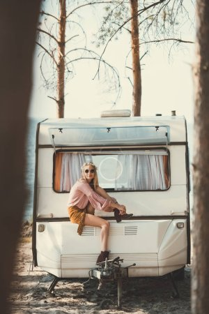 young hippie woman in wreath and sunglasses sitting on trailer