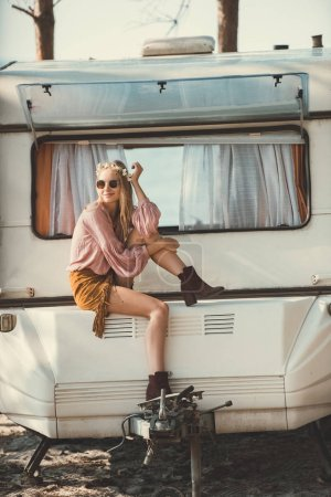 hippie girl in wreath and sunglasses sitting on campervan