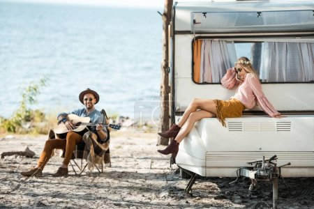 hippie girl sitting on campervan while man playing acoustic guitar near