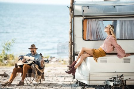 attractive girlfriend sitting on trailer while man playing guitar near the sea