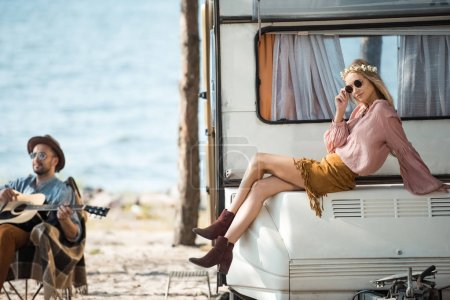 Photo for Hippie girl sitting on campervan while her boyfriend playing guitar near the sea - Royalty Free Image