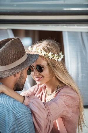 hippie couple in sunglasses embracing and looking at each other near trailer