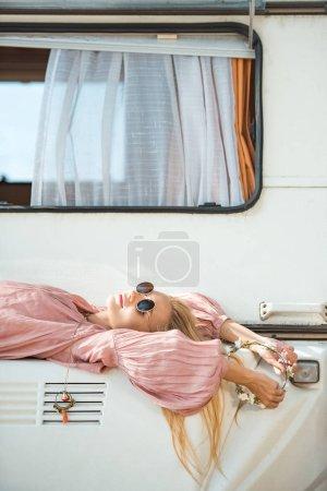 beautiful hippie girl in wreath and sunglasses lying on camper van