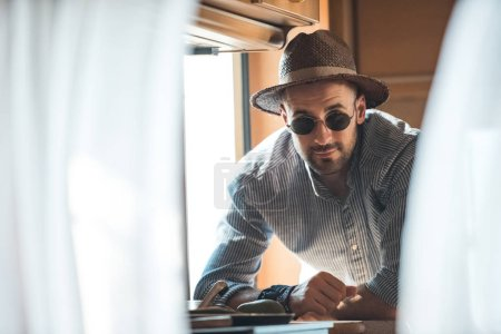 handsome man in sunglasses and hat looking at camera from trailer