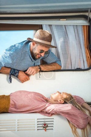 attractive hippie girl lying on trailer and man looking at her