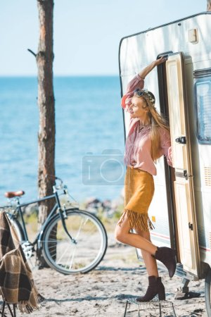 attractive hippie girl standing near camper van with bicycle