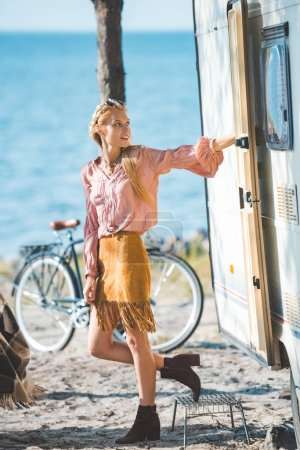 beautiful hippie girl standing near trailer with bicycle