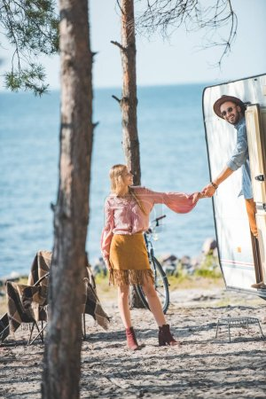 hippie couple holding hands and going for a walk at campervan near sea