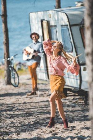 hippie girl dancing while man playing guitar near campervan