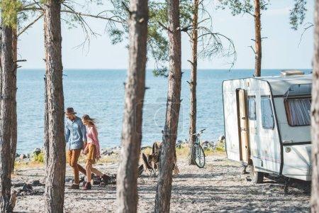 Photo pour Jeune couple tenant la main et marchant dans la nature près du camping-car - image libre de droit