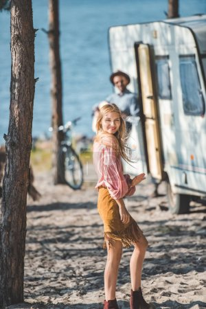 attractive young woman dancing while man playing guitar near campervan