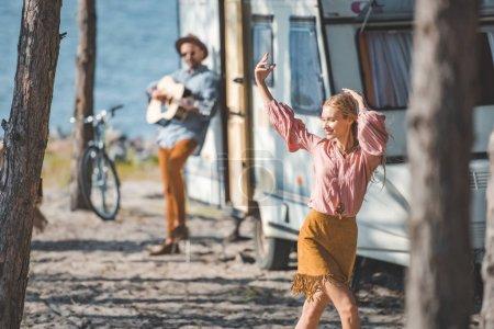 young hippie woman dancing while man playing guitar near trailer