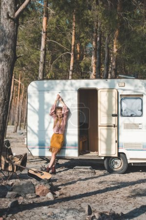 attractive hippie girl posing near campervan in forest