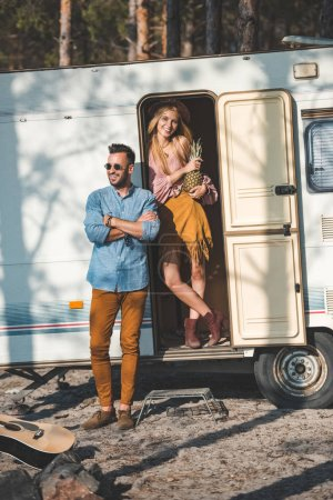 beautiful hippie couple with pineapple posing near campervan