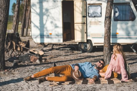 young happy couple relaxing on blanket near camper van