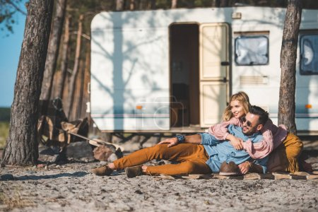 hippie young couple relaxing on blanket near camper van