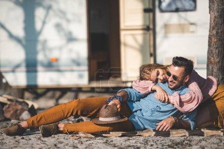hippie couple relaxing on blanket near camper van