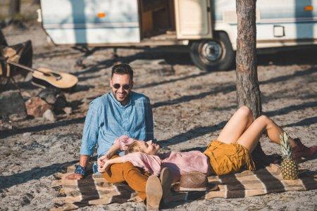 Photo pour Couple de hippie reposant sur la couverture près de remorque dans la nature - image libre de droit
