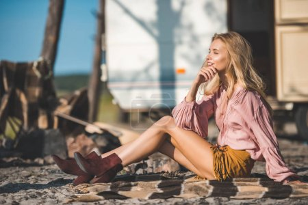 beautiful hippie girl resting on blanket near camper van