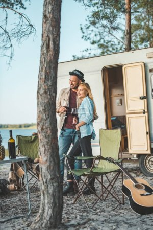 young couple with glasses of wine standing near campervan