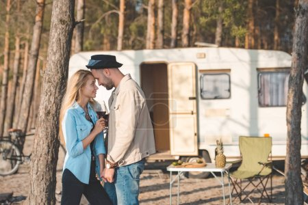 young couple touching the foreheads and holding glasses of wine near campervan