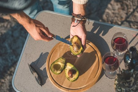 partial view of man cutting avocado on wooden board on table with wineglasses and sunglasses