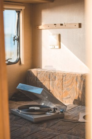 vintage vinyl player with record inside of campervan with sunlight