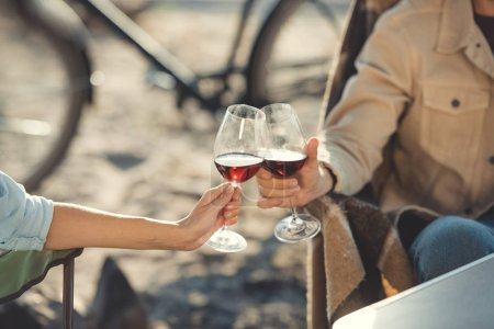partial view of couple clinking with glasses of wine during a picnic