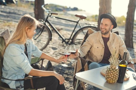 young beautiful couple clinking with glasses of wine during a picnic, bicycle on background