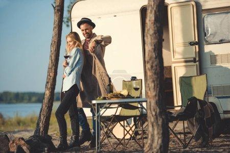 man wearing warm sweater on his girlfriend near campervan