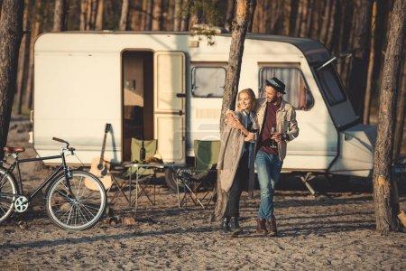 Photo pour Couple heureux avec des verres de vin marchant près de remorque dans le camp - image libre de droit