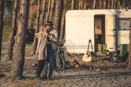 beautiful happy couple embracing in camp with trailer, bicycle and guitar