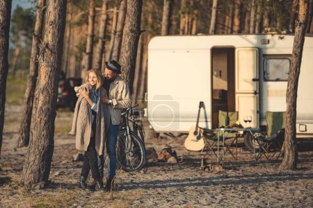 happy couple of lovers embracing in forest camp with trailer, bicycle and guitar
