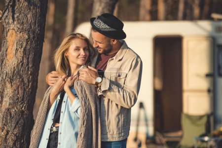 happy man hugging woman near campervan in forest