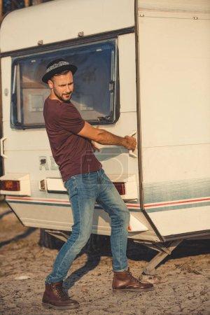 handsome man in hat trying to open door of campervan