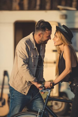 beautiful happy couple looking at each other standing together with bike near trailer