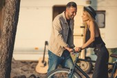 beautiful smiling couple standing together with bicycle near campervan