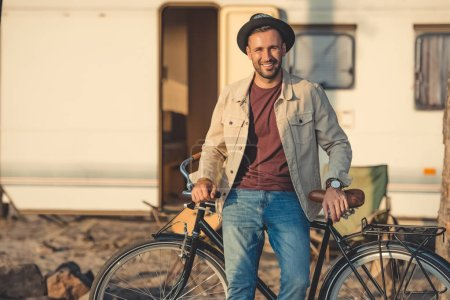 happy handsome man leaning on bicycle near trailer