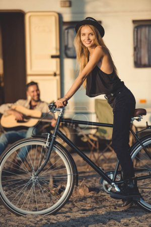 selective focus of attractive girl with bike and boyfriend playing guitar near camper van