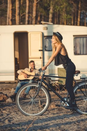 Photo for Selective focus of beautiful woman with bicycle and man playing guitar near campervan - Royalty Free Image