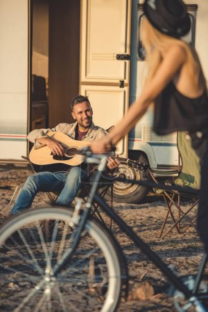 selective focus of girl with bicycle and man playing guitar near trailer