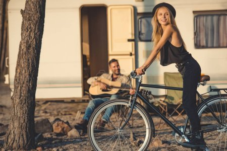 selective focus of happy girl with bicycle and man playing guitar near trailer