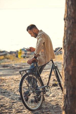 Photo pour Jeune homme à l'aide du gadget et se penchant sur la bicyclette près de mer - image libre de droit