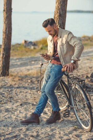 young man using smartphone and leaning on bicycle
