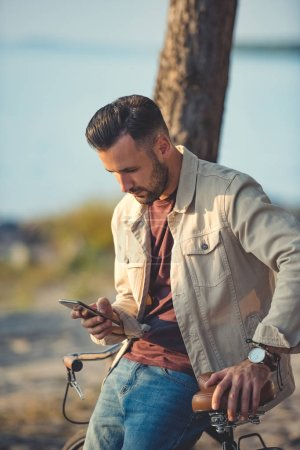 handsome man using smartphone and leaning on bicycle